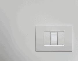 White three-way switch on a white wall